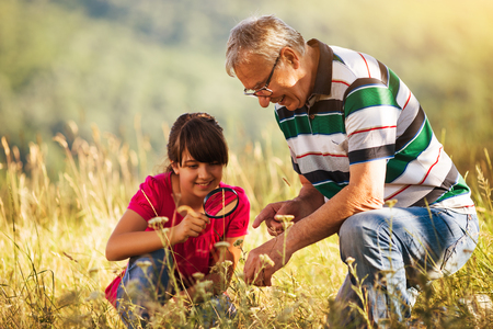 avocation: Happy grandfather and granddaughter explore together with magnifying glass nature.Image is intentionally toned.