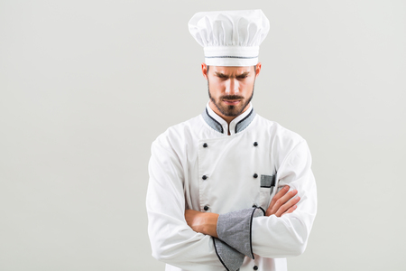 Angry chef on gray background.