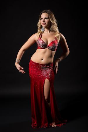 Bailarina de vientre hermosa que realiza danza de vientre en fondo negro.