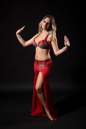 Bailarina de vientre hermosa que realiza danza de vientre en fondo negro. Foto de archivo