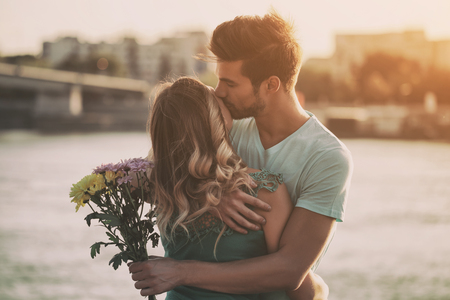 Młody mężczyzna daje swojej dziewczynie piękny bukiet kwiatów. Obraz jest celowo stonowany. Zdjęcie Seryjne
