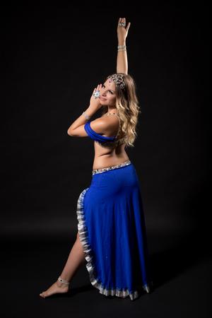 Dançarino de barriga bonito que executa a dança do ventre no fundo preto.