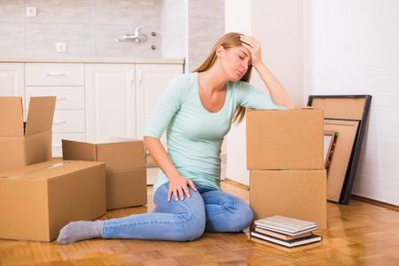 Overworked woman fell asleep on boxes while moving into new home.