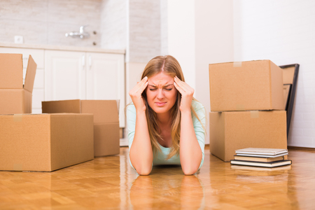 Woman is having headache because of moving into new home.