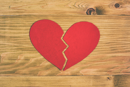 Broken heart on wooden table.Image is intentionally toned.