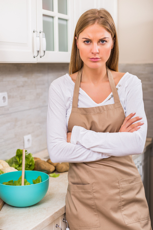 Angry woman standing  in her kitchen while making meal.
