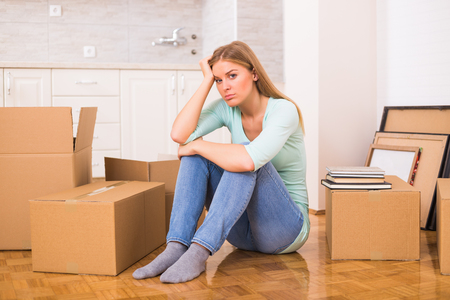 Tired woman sitting on the floor while moving into new home. Stock Photo