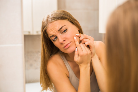 Young  woman squeezing pimple in the bathroom.