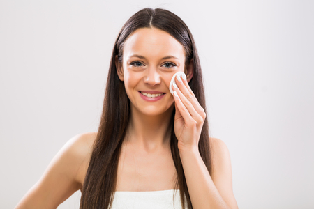 Beautiful brunette woman cleaning her face with cotton pad. Stock Photo