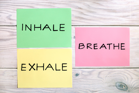 Words inhale,exhale and breath on wooden table.Image is intentionally toned.