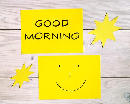 Envíe un mensaje de texto con buenos días y carita sonriente con formas de sol en la mesa de madera. La imagen está tonificada intencionalmente.