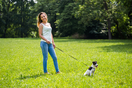 Beautiful woman enjoys walking with her  cute dog Jack Russell Terrier in the nature.