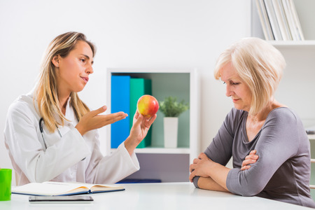 Senior woman patient refusing to eat fruit which is good for her health. Stock Photo