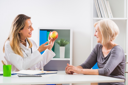 Female doctor is giving advice about eating healthy food to her senior woman patient . Archivio Fotografico
