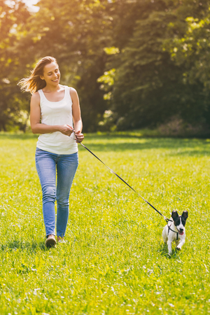 Beautiful woman enjoys walking with her  cute dog Jack Russell Terrier in the nature.Image is intentionally toned. Stock fotó