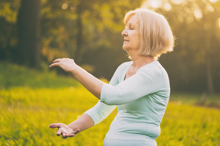 Senior woman enjoys exercise Tai Chi in the nature.Image is intentionally toned. Stock Photo
