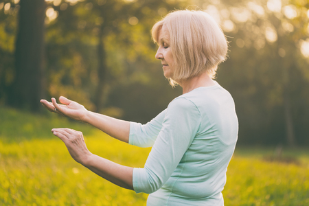 Ältere Frau trainiert gerne Tai Chi in der Natur. Das Bild ist absichtlich getönt.