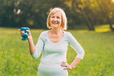Portrait of sporty senior woman holding weights outdoor.Image is intentionally toned.
