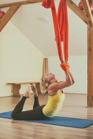 Woman doing aerial yoga in the fitness studio.Image is intentionally toned. Stock Photo