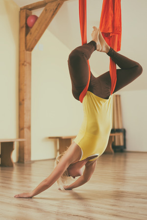 Woman doing aerial yoga in the fitness studio.Image is intentionally toned. 스톡 콘텐츠