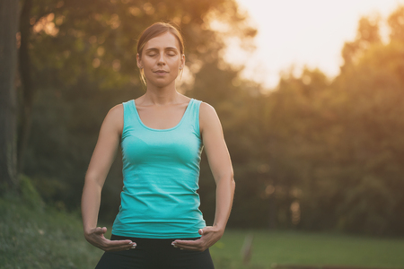 Beautiful woman enjoys exercising Tai Chi in the nature.Image is intentionally toned. Stock Photo