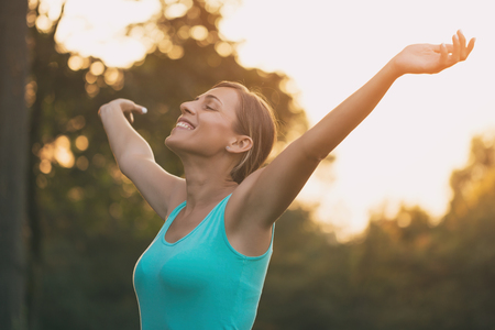 Beautiful sporty woman enjoys with her arms outstretched in the nature.Image is intentionally toned.