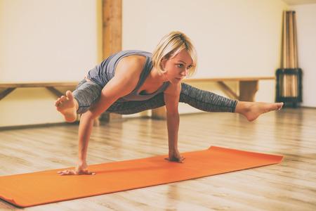 Woman doing yoga in studio,Tittibhasana Firefly Pose.Image is intentionally toned.