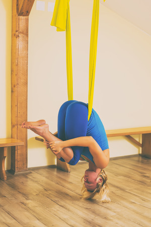 Woman doing aerial yoga in the fitness studio.Image is intentionally toned. 免版税图像 - 108426603