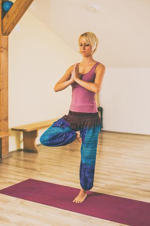 Woman doing yoga in studio,Tree poseVrikshasana.Image is intentionally toned.