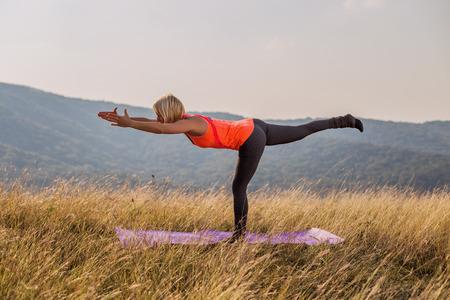 Beautiful woman doing yoga in the nature,Virabhadrasana III /Warrior Pose III.Image is intentionally toned.