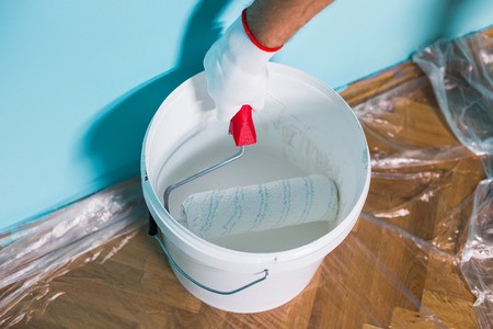 Image of paint can and man holding paint roller in front of blue wall. Stockfoto