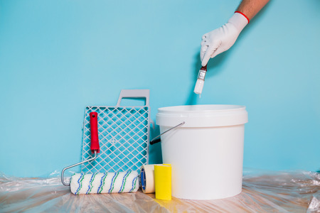 Image of equipment for painting wall and man holding paintbrush.