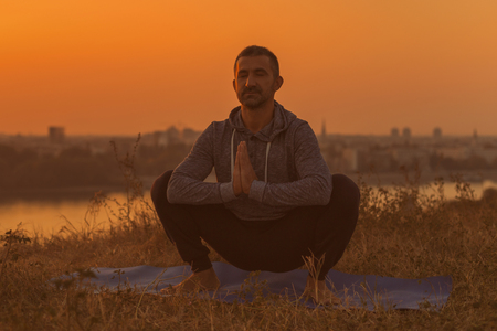 Man doing yoga on sunset with city view,Utkatasana/Buddhist stupa pose .Toned image.
