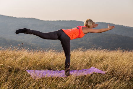 Beautiful woman doing yoga in the nature,Virabhadrasana III Warrior Pose III.Image is intentionally toned. Stock Photo