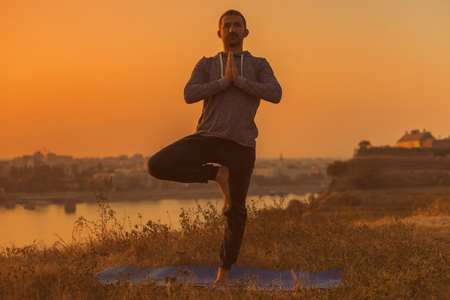 Man doing yoga on sunset with city view,Tree poseVrikshasana.Toned image. Stock Photo