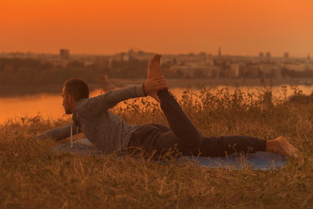 Man doing yoga on sunset with city view,Half Bow PoseArdha Dhanurasana. Toned image. Stock Photo