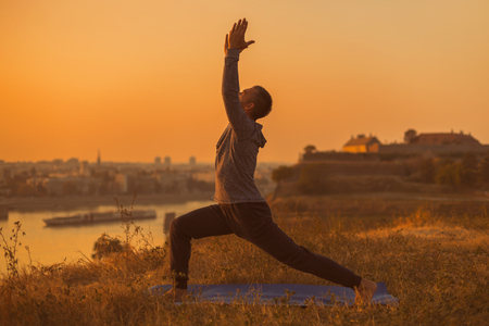 Man doing yoga on sunset with city view, Warrior 1 Pose/ Virabhadrasana I.Toned image. Stockfoto