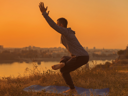 Man doing yoga on sunset with city view, variation of Chair Pose Utkatasana.  Toned image.
