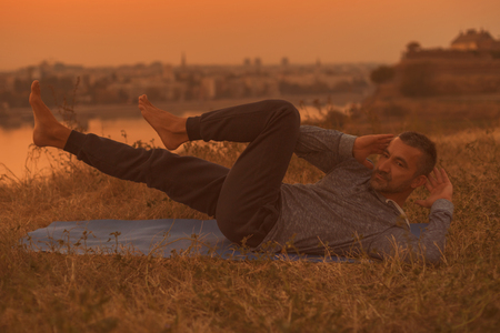 Man  exercising on sunset with city view.Toned image. Stock Photo