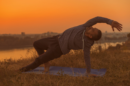 Man doing yoga on sunset with city view,variation of Side Plank PoseVasisthasana. Toned image.