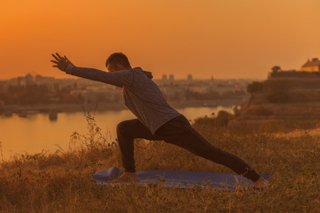 Man doing yoga on sunset with city view, Low Pyramid Pose Parsvottanasana.Toned image. Stock Photo