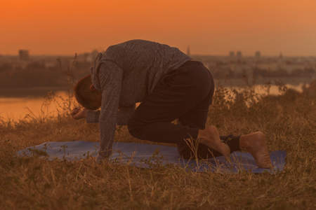 Man doing yoga on sunset with city view.Toned image.