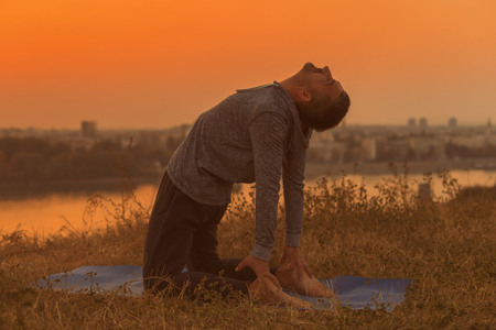 Man doing yoga on sunset with city view,Camel Pose Ustrasana.Toned image.