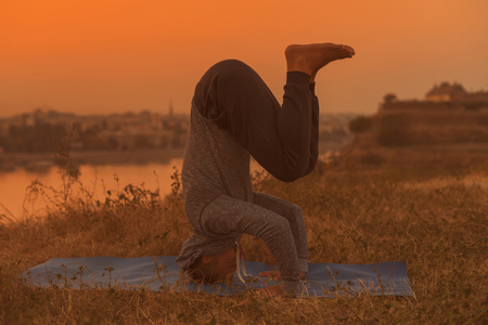Man doing yoga on sunset with city view,Headstand Shirshasana.Toned image.
