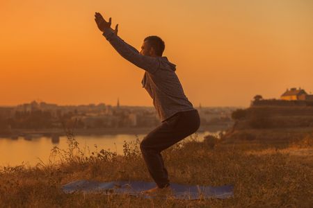Man doing yoga on sunset with city view,Chair Pose Utkatasana.  Toned image.