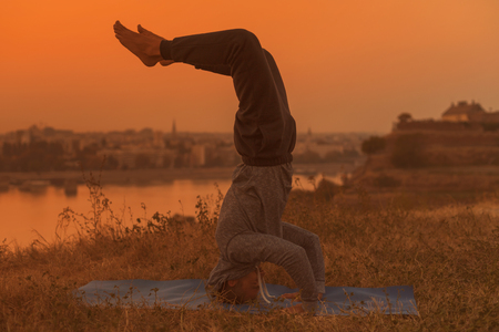 Man doing yoga on sunset with city view,VrschikasanaScorpion pose .Toned image.