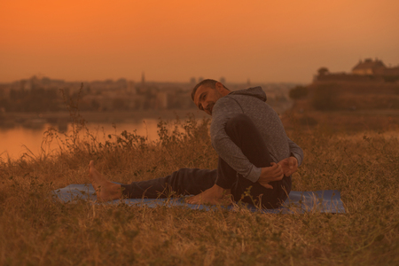 Man doing yoga on sunset with city view, variation of Half Lord of the Fishes Pose Ardha Matsyendrasana. Toned image.