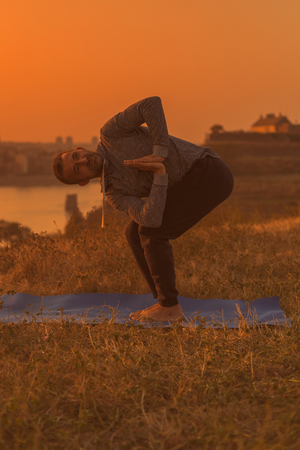 Man doing yoga on sunset with city view, Revolved Chair Pose  Parivrtta Utkatasana.Toned image.