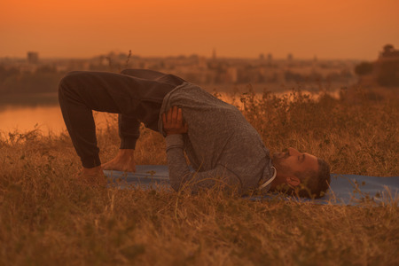 Man doing yoga on sunset with city view, Setu Bandha SarvangasanaSupported Bridge PoseToned image.