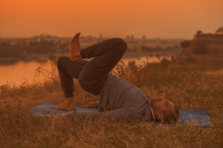 Man doing yoga on sunset with city view,One Legged Bridge Pose  Eka Pada Setubandha Sarvangasana.Toned image.